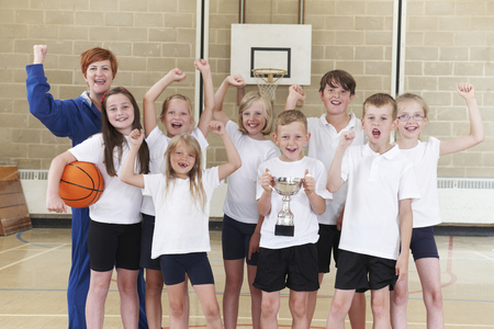 basketball girl: Escuela de Baloncesto Tean Y Entrenador Celebraci�n de la victoria con el trofeo Foto de archivo