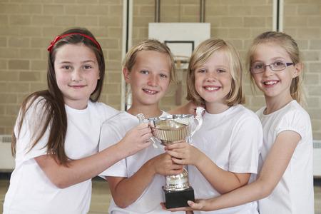 school sports: Female School Sports Team In Gym With Trophy