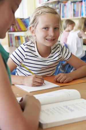 niño escuela: Escuela Primaria alumno trabaja en el escritorio en sala de clase