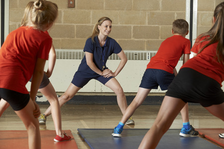 gym: Teacher Taking Exercise Class In School Gym