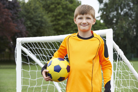 goal keeper: Portrait Of Goal Keeper Holding Ball On School Soccer Pitch Stock Photo