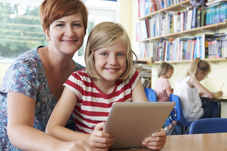 School Pupil With Teacher Using Digital Tablet Computer In Classroom photo