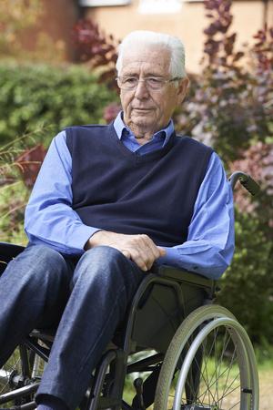 paraplegic: Deprimido hombre mayor sentado al aire libre en silla de ruedas