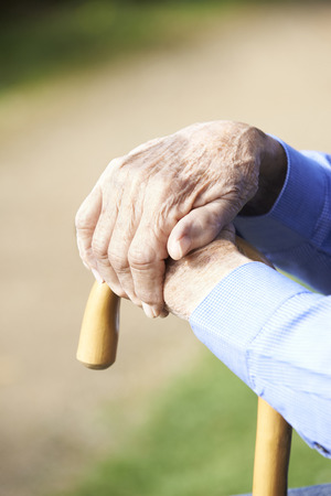 on hands: Close Up Of Senior Mans Hands Resting On Walking Stick