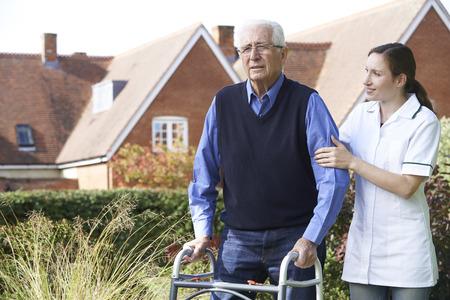 adult 80s: Carer Helping Senior Man To Walk In Garden Using Walking Frame