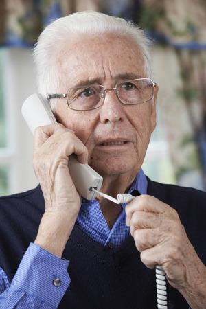 answering: Worried Senior Man Answering Telephone At Home