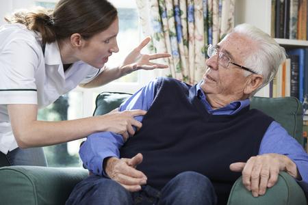 violencia intrafamiliar: Cuidado Trabajador maltratar hombre mayor en el hogar Foto de archivo