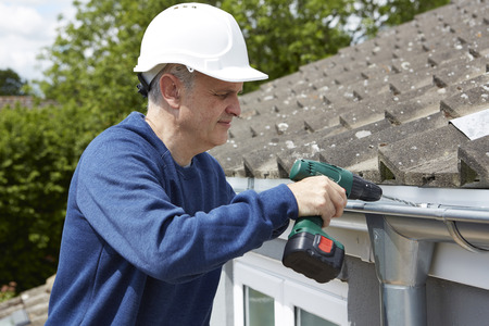 roofs: Workman Replacing Guttering On Exterior Of House