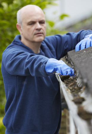 clearing: Man Clearing Leaves From Guttering Of House