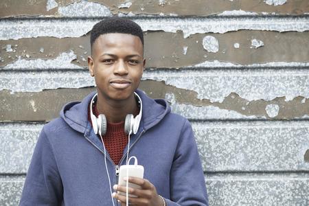 adolescente: Adolescente con audífonos y escuchar la música en el ambiente urbano Foto de archivo