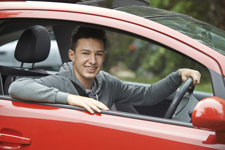 passed: Newly Qualified Teenage Boy Driver Sitting In Car