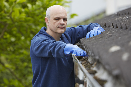 fall leaves: Man Clearing Leaves From Guttering Of House