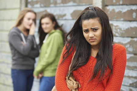 abused women: Unhappy Teenage Girl Being Gossiped About By Peers