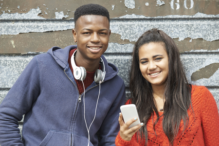 smiling teenagers: Teenager Couple Sharing Text Message On Mobile Phone