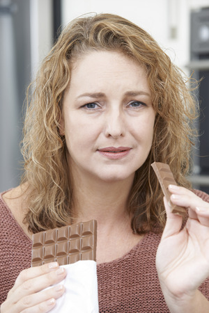 fedup: Guilty Woman On Diet Eating Chocolate Bar At Home