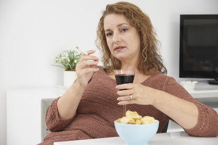 social drinking: Woman Smoking Cigarette Whilst Drinking Wine And Eating Snacks Stock Photo