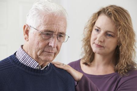 tercera edad: Hombre mayor serio con la hija adulta en el hogar