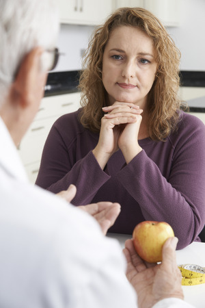 a lady doctor: Plus Size Woman In Meeting With Dietitian Stock Photo