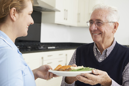 care in the community: Carer Serving Lunch To Senior Man