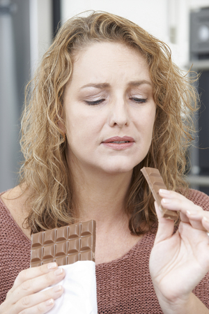 woman eating: Guilty Woman On Diet Eating Chocolate Bar At Home