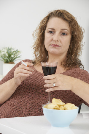 whilst: Woman Smoking Cigarette Whilst Drinking Wine And Eating Snacks Stock Photo