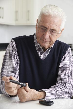 blood sugar level: Senior Man Checking Blood Sugar Level At Home Stock Photo