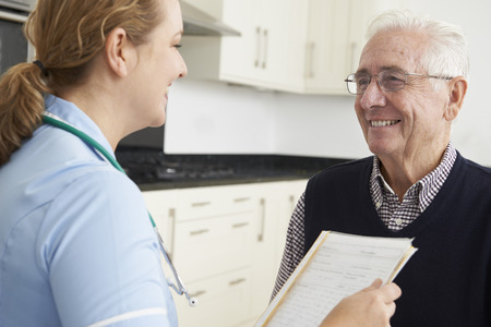 nursing record: Nurse Discussing Medical Record With Senior Male Patient Stock Photo