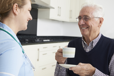 home visit: Nurse Chatting With Senior Man During Home Visit Stock Photo
