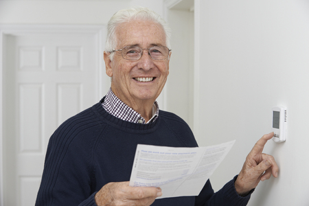 thermostat: Smiling Senior Man With Bill Adjusting Central Heating Thermostat