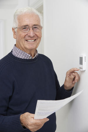 money and saving: Smiling Senior Man With Bill Adjusting Central Heating Thermostat