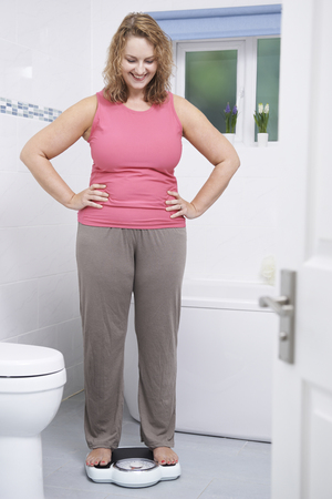 woman on scale: Happy Woman Weighing Herself On Scales In Bathroom Stock Photo