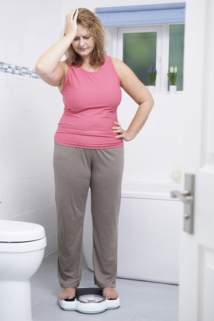 binge: Overweight Woman Weighing Herself On Scales In Bathroom