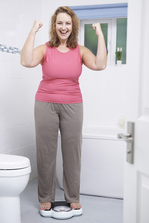 Caucasian woman: Happy Woman Weighing Herself On Scales In Bathroom Stock Photo
