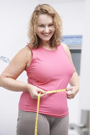 woman measuring waist: Happy Plus Size Woman Measuring Waist In Bathroom