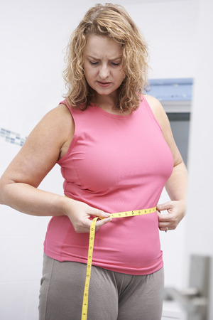 woman measuring waist: Frustrated Overweight Woman Measuring Waist In Bathroom