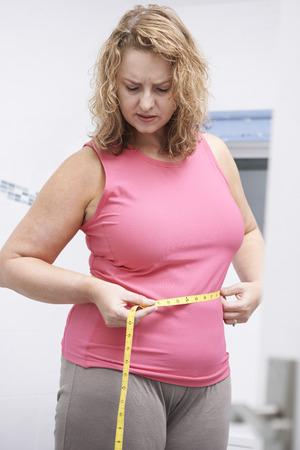 binge: Frustrated Overweight Woman Measuring Waist In Bathroom