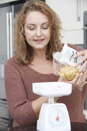 measuring: Plus Size Woman On Diet Weighing Out Pasta For Meal Stock Photo
