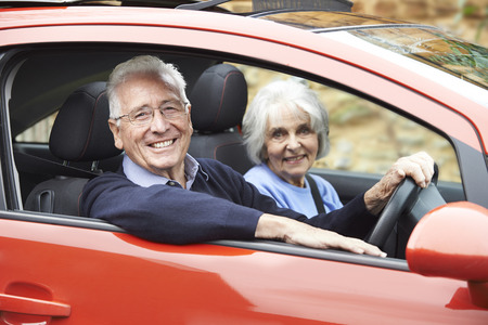 female driver: Portrait Of Smiling Senior Couple Out For Drive In Car