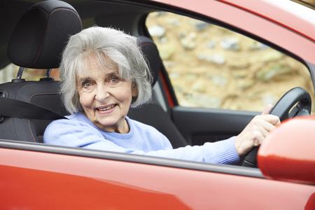 old car: Portrait Of Smiling Senior Woman Driving Car