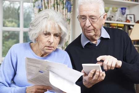 home finances: Senior Couple At Home With Bills Worried About Home Finances