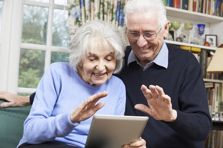 video call: Senior Couple Using Digital Tablet For Video Call With Family