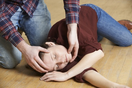 position: Man Placing Woman In Recovery Position After Accident Stock Photo