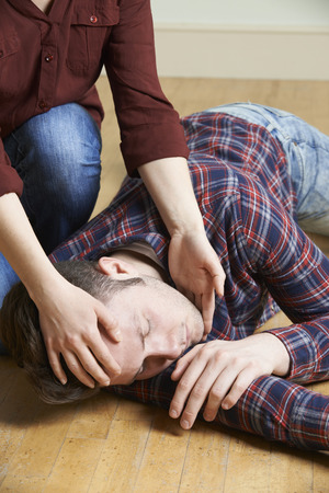 two person: Woman Placing Man In Recovery Position After Accident Stock Photo