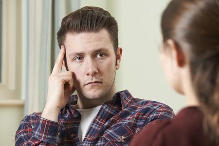 dos personas platicando: Deprimido hombre joven que habla con el consejero