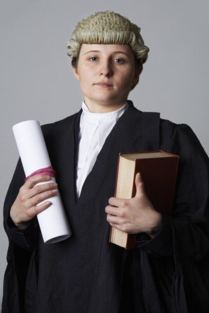 Studio Portrait Of Female Lawyer Holding Brief And Book