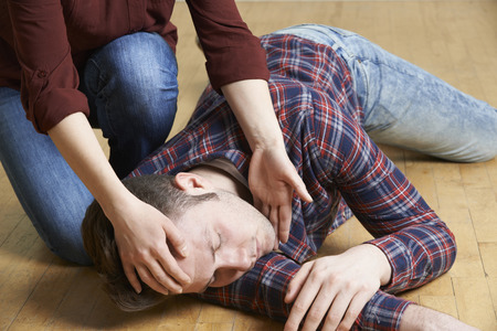 safety first: Woman Placing Man In Recovery Position After Accident Stock Photo