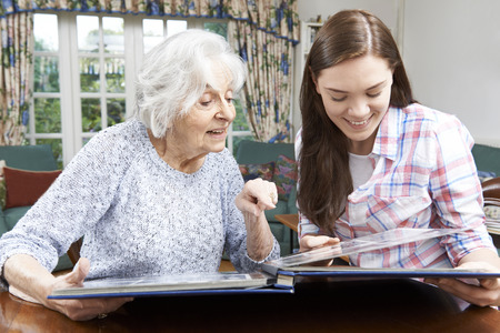 Grandmother Looking At Photo Album With Teenage Granddaughter Standard-Bild