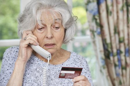 Hogere vrouw die Credit Card Details Op De Telefoon