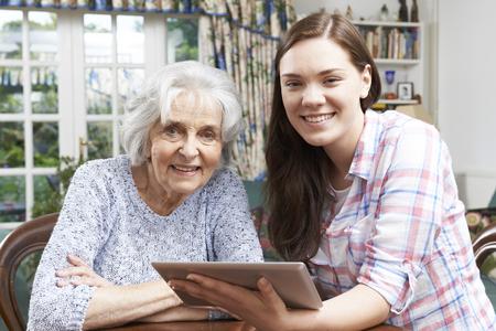 helping: Adolescente Nieta Mostrando Abuela Cómo utilizar la tableta digital