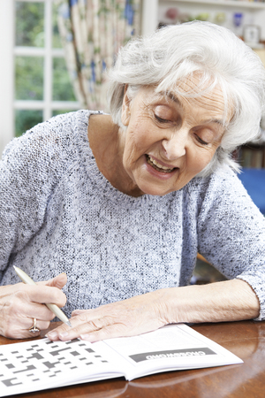 Senior Woman Relaxing With Crossword Puzzle At Home Stok Fotoğraf - 46634234